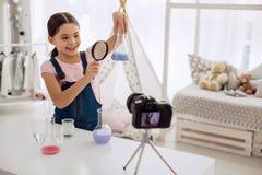 Śliczna dziewczyna egzamininuje rezultat chemiczny eksperyment podczas gdy nagrywający vlog fotografia stock