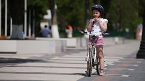 Śliczna dziewczyna jest ubranym hełm i wtedy jedzie bicykl w parku w światło słoneczne dniu zdjęcie wideo
