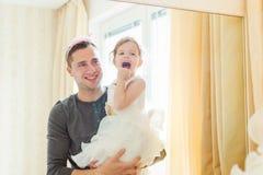 Śliczna dziewczyna która stawia dalej uzupełniał na jej ojcu fotografia stock
