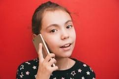 Śliczna dziewczyna opowiada na urządzeniu przenośnym na czerwonym tle obraz stock