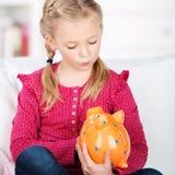 Śliczna dziewczyna patrzeje prosiątko banka Fotografia Stock