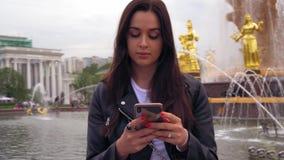 Śliczna dziewczyna patrzeje wokoło i pisać na maszynie na telefonie komórkowym w eleganckich ubraniach 4K zdjęcie wideo