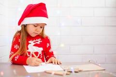 Śliczna dziewczyna pisze liście Santa, biały tło obraz stock