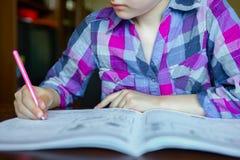 Śliczna dziewczyna pisze pracie domowej przy jego biurkiem obraz stock