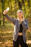 Śliczna dziewczyna pokazuje jej jęzor i pokazuje dwa f podczas gdy ona istny selfie obraz stock