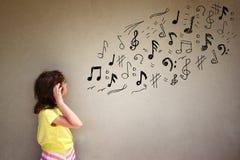 Śliczna dziewczyna słucha muzyczne notatki obok textured tła obraz royalty free