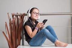Śliczna dziewczyna słucha muzyka z szkłami fotografia stock