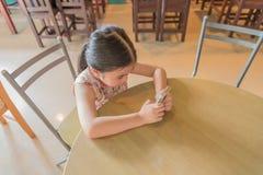 Śliczna dziewczyna, siedzący sztuki smartphone na krześle w restauraci Obraz Stock