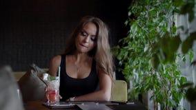Śliczna dziewczyna siedzi w kawiarni i ma zimnego napój salowego zbiory wideo