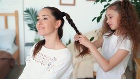 Śliczna dziewczyna splata jej mama włosy w warkoczu, ostrość na córce, zwolnione tempo zbiory
