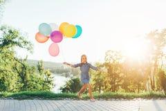 Śliczna dziewczyna trzyma kolorowych balony w miasto parku, bawić się zdjęcie royalty free