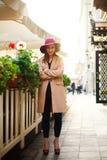 Śliczna dziewczyna w żakiecie na ulicznym turystycznym miasteczku z kwiatami na zmierzchu Zdjęcie Royalty Free