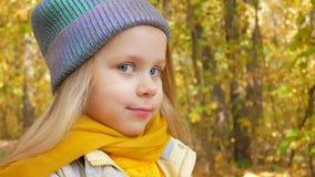 Śliczna dziewczyna w błękitnym koloru kapeluszu neonowym koloru żółtego szaliku i jest uśmiechnięta przy parkiem w jesieni zbiory