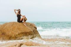 Śliczna dziewczyna w czarnej lato sukni przy dużymi kamieniami Zdjęcie Stock
