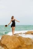 Śliczna dziewczyna w czarnej lato sukni przy dużymi kamieniami Fotografia Royalty Free