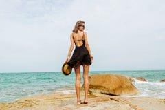 Śliczna dziewczyna w czarnej lato sukni przy dużymi kamieniami Fotografia Stock