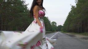 Śliczna dziewczyna w długiej sukni wiruje na drodze zdjęcie wideo