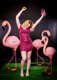 Śliczna dziewczyna w fuksja cekinach ubiera odpoczywać i tanczyć z trzy dużymi flamingami na czarnym tle obrazy stock