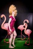 Śliczna dziewczyna w fuksja cekinach ubiera odpoczywać i tanczyć z trzy dużymi flamingami na czarnym tle fotografia royalty free