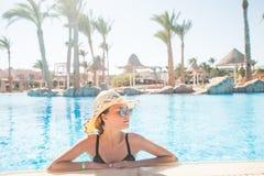 Śliczna dziewczyna w kapeluszu i okularach przeciwsłonecznych w pływackim basenie z kopii przestrzenią Lata powołanie fotografia stock