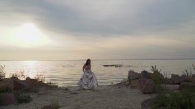 Śliczna dziewczyna w modnej sukni na pięknej plaży zbiory wideo