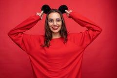 Śliczna dziewczyna w mysz ucho pozuje na czerwonym tle ilustracji