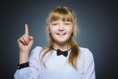 Śliczna dziewczyna wskazuje up z palcem na szarym tle z zaskakującym wyrażeniem zdjęcia royalty free