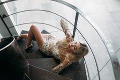Śliczna dziewczyna z piękną postacią w krótkiej błyszczącej sukni kłama na czarnym schody Portret elegancka seksowna dziewczyna w Zdjęcia Royalty Free