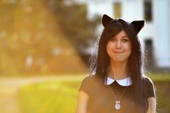 Śliczna dziewczyna z zabawkarskimi kotów ucho na głowie w sunbeam świetle Obrazy Royalty Free