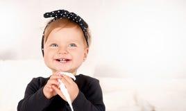 Śliczna dziewczynka ubierał w czarnej sukni na światła białego tle Obraz Royalty Free