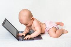 Śliczna dziewczynka w pieluszce bawić się z laptopem Zdjęcie Stock