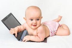 Śliczna dziewczynka w pieluszce bawić się z laptopem Obraz Stock