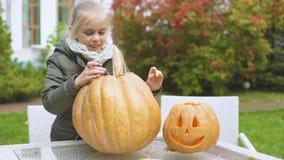 Śliczna emocjonalna dziewczyna rzeźbi dyniowego lampion excited z proces Halloween zbiory wideo