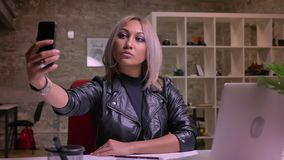 Śliczna entuzjastyczna caucasian blondynki kobieta w brać selfies na ona telefon podczas gdy siedzący przy desktop podczas gdy si