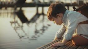 Śliczna Europejska chłopiec bawić się z jezioro wodą na molu Mały męski dziecko z plecaka lata rekonesansową naturą 4K zakończeni zbiory