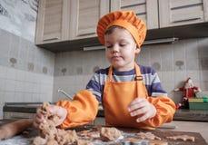 Śliczna Europejska chłopiec w kostiumu kucharz robi imbirowym ciastkom fotografia royalty free