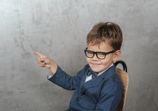 Śliczna Europejska chłopiec w kurtce z motylem wskazuje jego palec przy ścianą obrazy royalty free