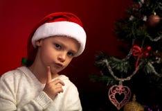 Śliczna gniewna dziewczyna w futerkowym Santa Claus kapeluszu blisko Bożenarodzeniowego holida Fotografia Stock