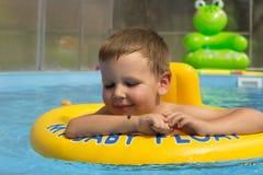 Śliczna i śmieszna mała dziewczynka w basenie, pływa w nadmuchiwanym pierścionku, styl życia pojęcie Nadmuchiwany okrąg Lato base obrazy stock