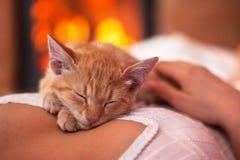 Śliczna imbirowa figlarka relaksuje - śpiący na kobiety klatce piersiowej w przodzie o zdjęcia royalty free