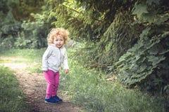 Śliczna kędzierzawa dziecko dziewczyna chodzi samotnie w lesie na footpath wśród drzew podczas wakacji letnich symbolizuje szczęś Obraz Royalty Free
