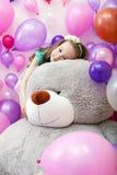 Śliczna kędzierzawa dziewczyna pozuje kłamać na dużym mokietu niedźwiedziu Zdjęcie Stock