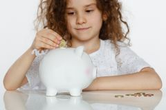 Śliczna kędzierzawa małej dziewczynki kładzenia moneta w dużego białego prosiątko banka nad białym tłem, Edukacyjny, ratujący pie obrazy stock
