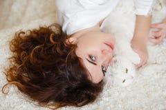 Śliczna kędzierzawego włosy kobieta w białej jedwabniczej opatrunkowej todze w wczesnym poranku bawić się z białym puszystym kota Obrazy Stock