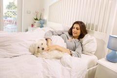Śliczna kobieta bawić się z psem w łóżku w domu Fotografia Royalty Free