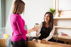 Śliczna kobieta kupuje gorącej herbaty przy kawiarnią zdjęcia stock