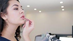 Śliczna kobieta robi makijażowi przed lustrem indoors na unfocused tle zbiory wideo