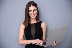 Śliczna kobieta stoi nad szarym tłem z laptopem Obraz Royalty Free