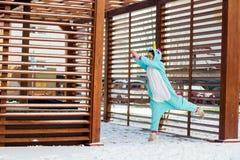 Śliczna kobieta w kigurumi jednorożec kostiumowym skoku jak bohater fotografia stock