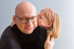 Śliczna kochająca mała dziewczynka całuje jej ojczulka zdjęcia stock